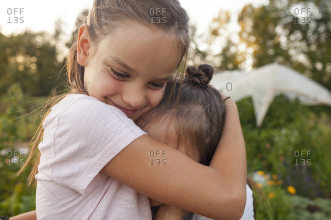 Portrait Of Two Sisters Hugging In The Garden In Fort Langley