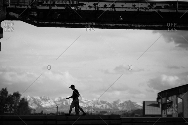 Silhouette Of Skateboarder Is Carrying His Skateboard