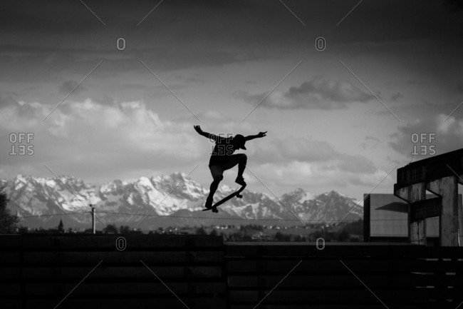 Silhouette Of Skateboarder Is Jumping Over Concrete Slabs
