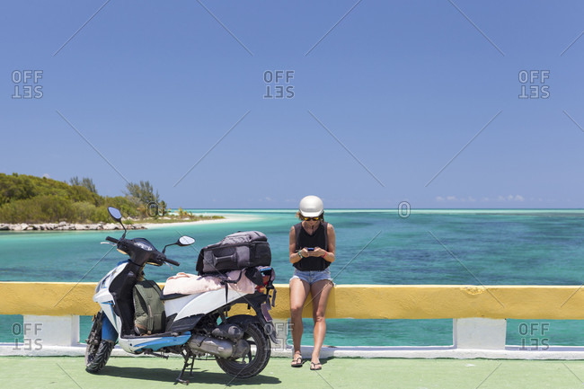 Girl Wearing A Scooter Helmet And Sunglasses Texting On Her Smartphone