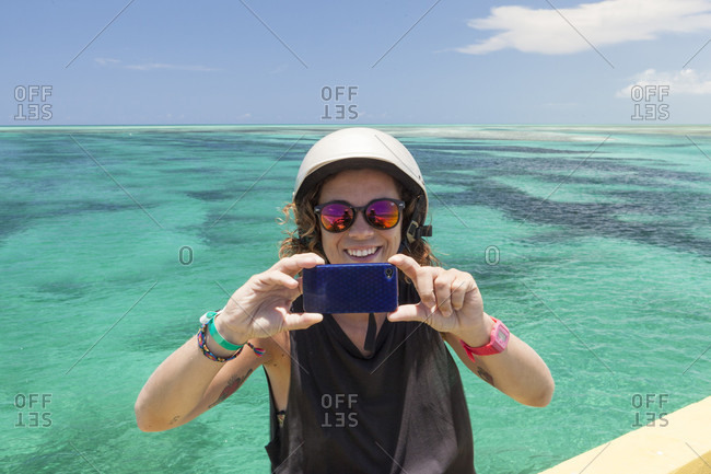 Girl Taking A Selfie With Her Smartphone With A Beautiful Crystal Blue Water On Her Background