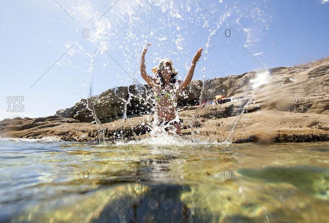 Woman Splashing Water In The Beach