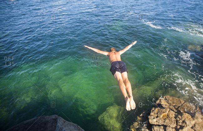 Shirtless Man Jumping In The Ocean Water