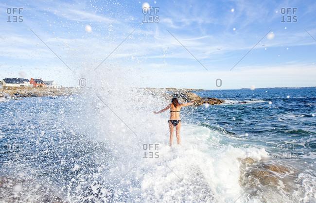 Woman Walking In Splashing Water Of Ile De Croix, France