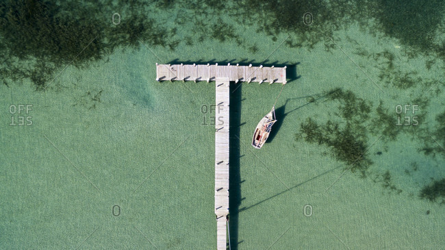 An Aerial View Of A Jetty And A Sailboat With Green Waters And Seaweed Visible