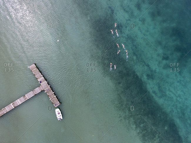 An Aerial View Of A Jetty With A Motor Boat With A Women Swimming In The Ocean