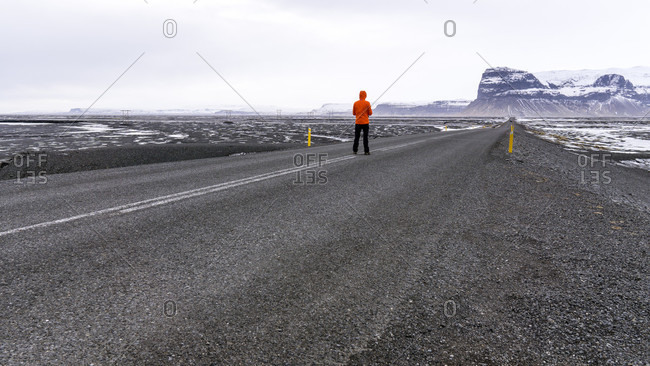 A Man Standing In The Middle Of The Road With Mountains In The Distance