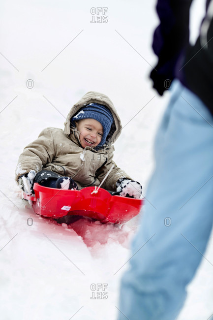 A Laughing Toddler Being Pulled In A Bright Red Sledge Across The Snow