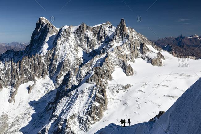 Alpine Climbers Making Their Way Along A Ridge Just Below The Aiguille Du Midi