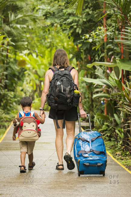 Rear View Of Mother And Son With Their Luggage In Tortuguero National Park