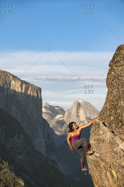 Female Climber Climbing On Rock In Yosemite With El Capitan And Half Dome In Background
