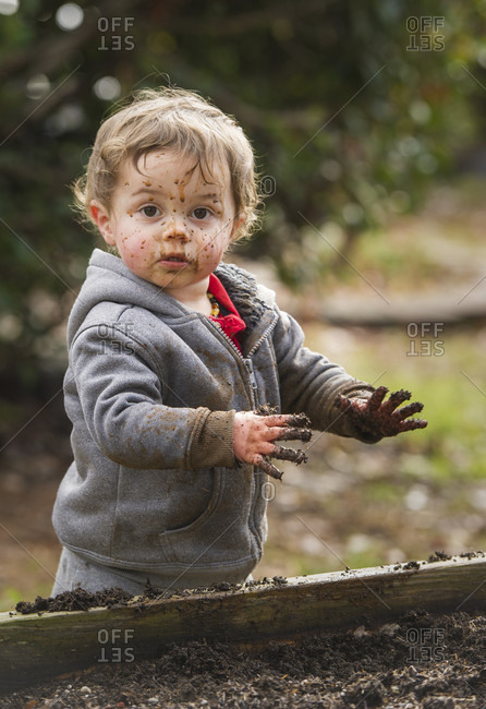 Portrait Of A Young Boy Playing In The Garden