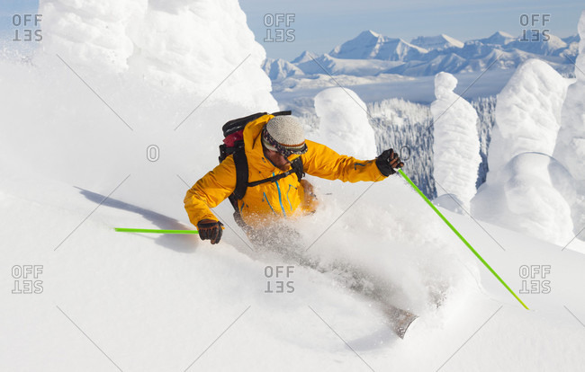Male Skier Making A Deep Powder Turn With Glacier National Park In The Background