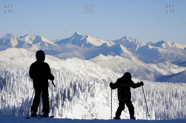 Silhouette Of Young Skiers Standing On Top Of Snowy Landscape