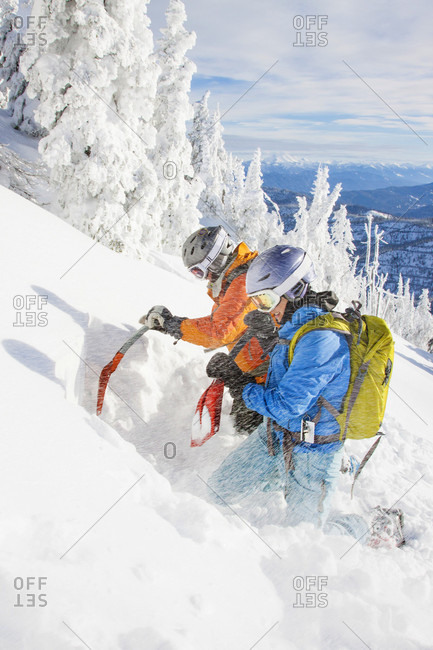 Two Female Backcountry Skiers Dig An Extended Column Test Snow Pit To Judge The Avalanche Risk In Montana