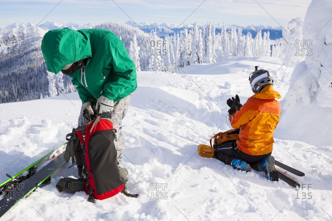 Male And Female Skier Packs Their Backpack After Skinning Near Whitefish, Montana, Usa