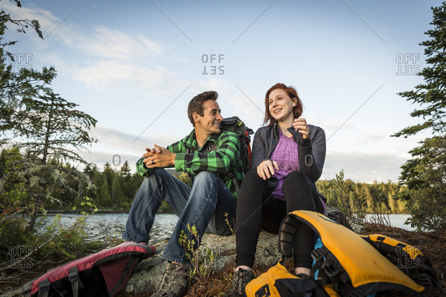 A Young Couple Take A Break From Paddling A Canoe On Long Pond