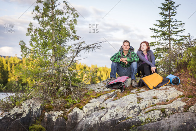 A Young Couple Take A Break From Paddling A Canoe On Long Pond In Maine's North Woods