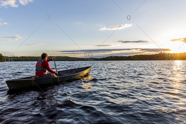 A Man Paddles His Canoe On Long Pond At Sunrise In Maine's North Woods Near Greenville, Maine