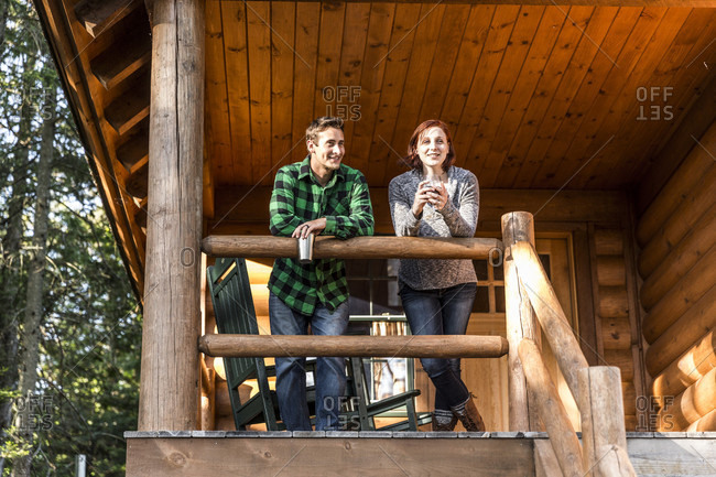 A Young Couple Enjoy An Evening On The Porch Of A Cabin At The Lodge Near Greenville, Maine