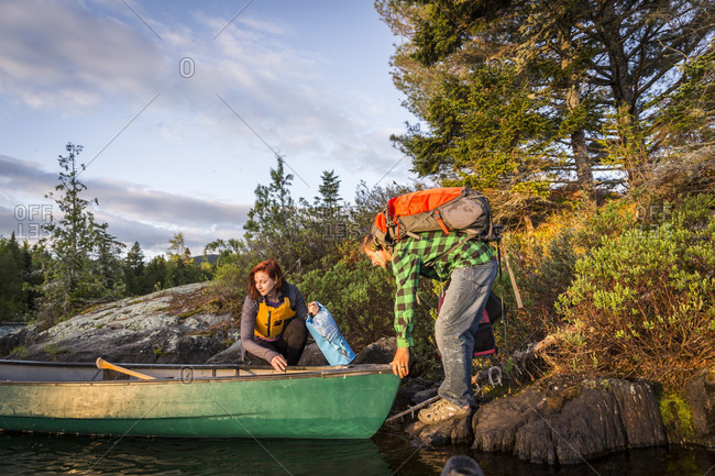 A Young Couple Take A Break From Paddling A Canoe On Long Pond In Maine's North Woods Near Greenville, Maine