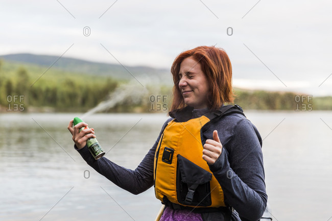 A Woman Applies Some Bug Spray Before A Morning Paddle On Long Pond