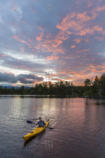 A Man Paddles His Kayak On Long Pond In Maine's North Woods Near Greenville, Maine