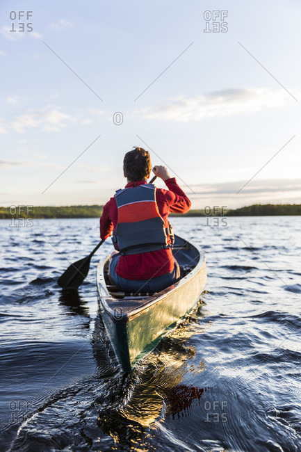 A Man Paddles His Canoe On Long Pond In Maine's North Woods Near Greenville, Maine