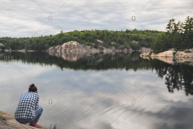 Young Woman Relaxing By A Lake On A Calm Summer Evening
