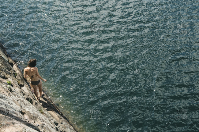 Young Woman On The Rock Ledge Ready To Jump In Water