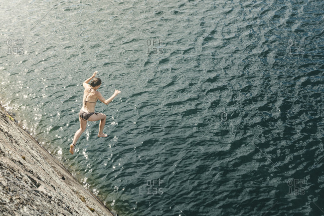 Young Woman Jumping Off A Cliff Into A Lake