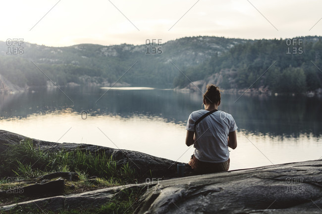 A Young Woman Is Sitting By The Lake At Dusk And Looking At Pictures On Her Camera