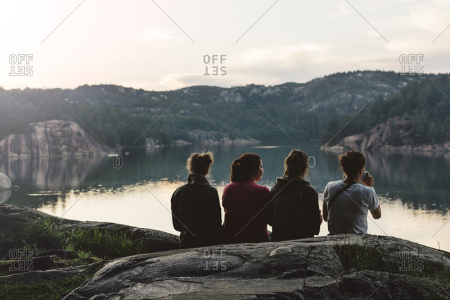 Four Young Women Are Sitting And Relaxing By The Lake At Dusk
