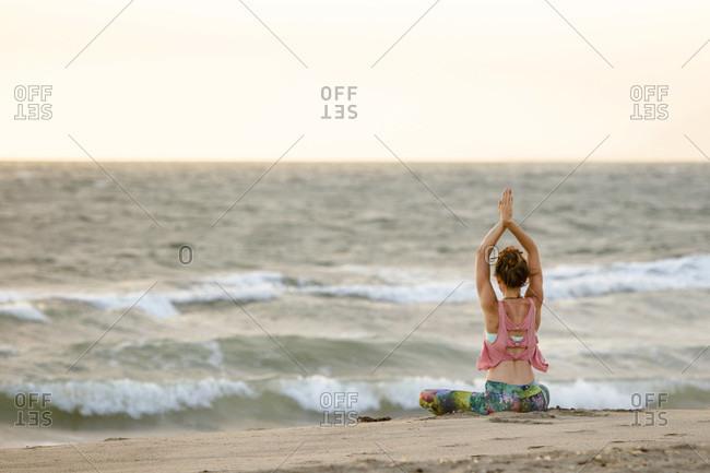 Woman Doing Yoga On Beach Sitting Cross Legged With Hands Above Head
