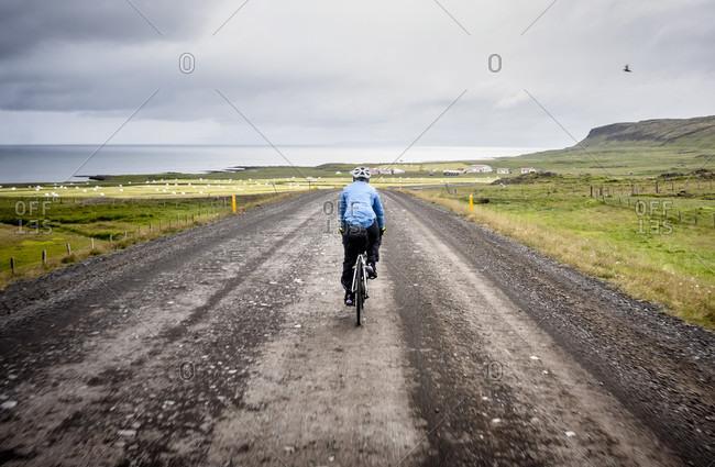 A Cyclist Rides On A Gravel Road Near Holmavik, Iceland
