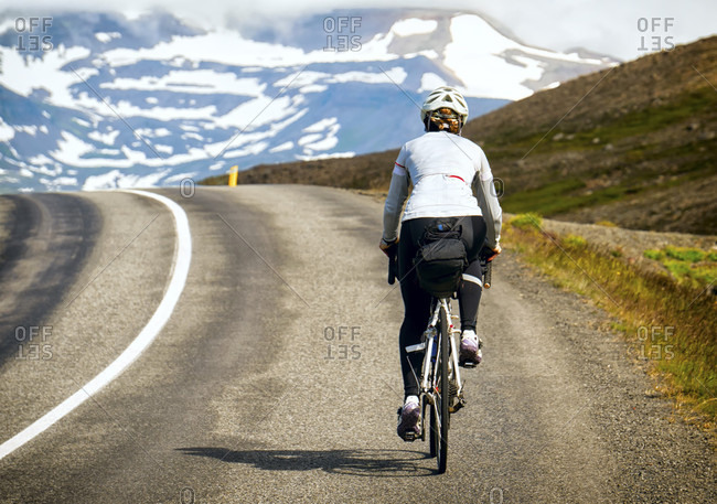 A Cyclist Rides Over The Top Of A Climb With Snowy Mountains In The Background