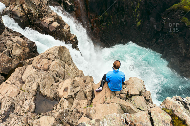 A Cyclist Sits On A Cliff Above A Waterfall In Iceland