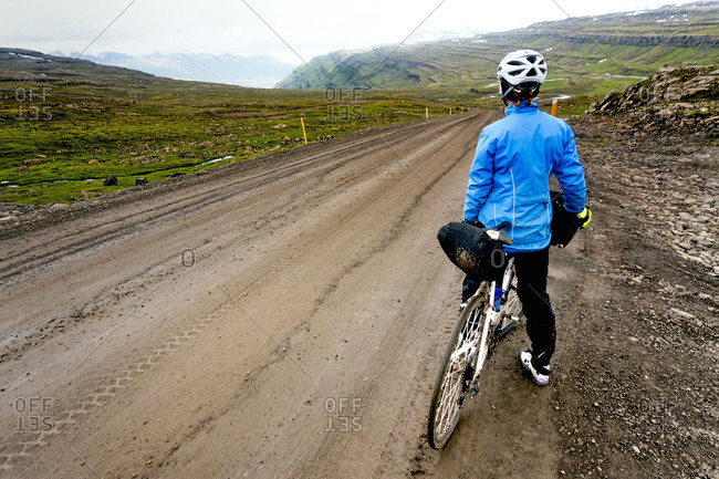 A Woman Cyclist Stops For A Break On The Side Of The Road In Iceland