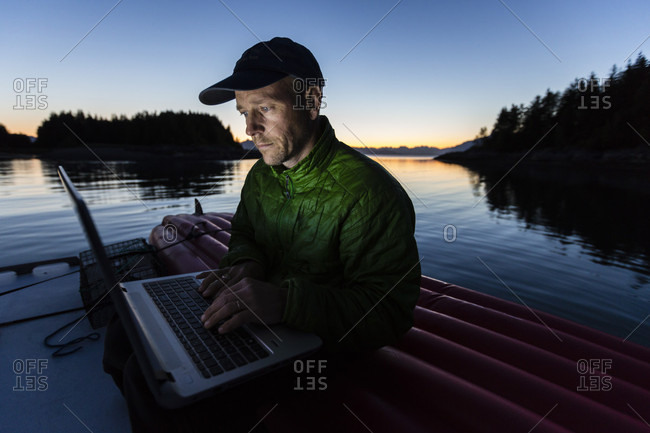 A Man Is Sitting On The Roof Of His Boat Working On Laptop In Johnson Cove, Alaska, Usa