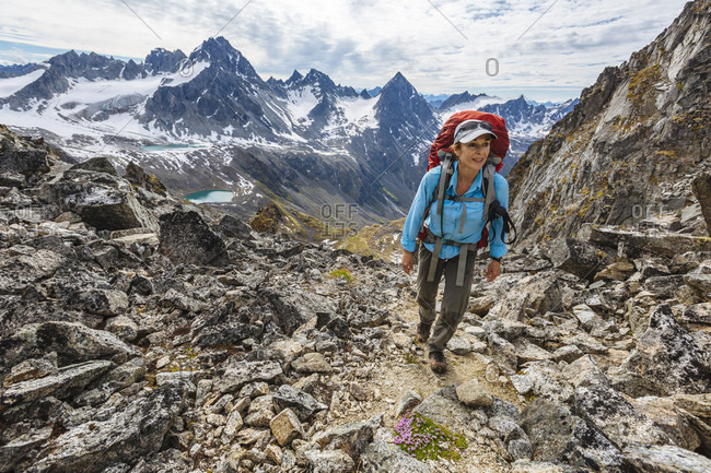 A Woman Hiking On Rocky Landscape In Talkeetna Range In Alaska, Usa