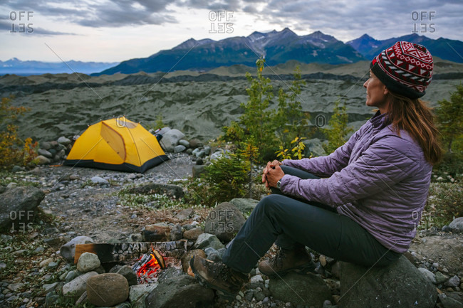 Woman Sitting By A Campfire Above The Root Glacier In Alaska, Usa