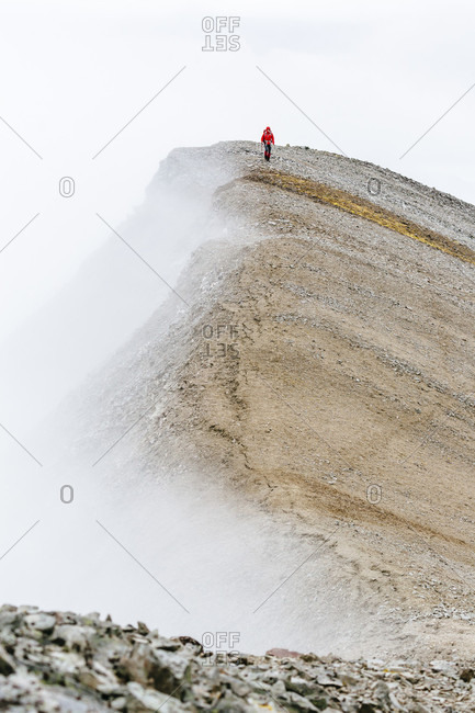 A Woman Is Hiking On A Ridge During Fog In The Delta Mountains, Alaska Range, Alaska, Usa