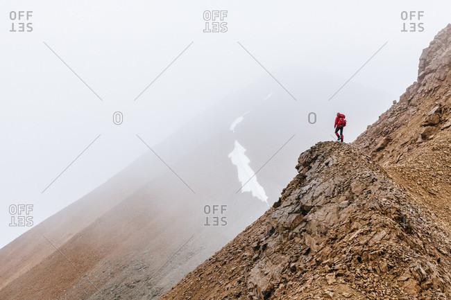 A Woman Is Hiking On A Ridge In Fog In The Delta Mountains, Alaska Range, Alaska, Usa