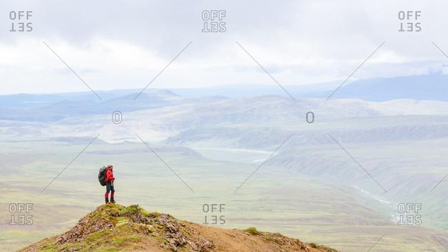 Female Hiker Standing On Top Of Mountain Exploring Alaska Range In Alaska, Usa