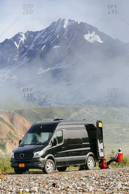 A Woman Sitting In A Chair Near Van Parked Off Road In Alaska, Usa