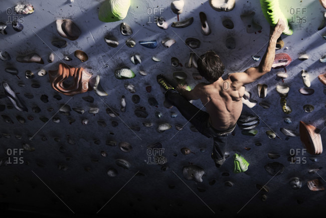 Shirtless Male Athlete Climbing On Indoor Climbing Wall