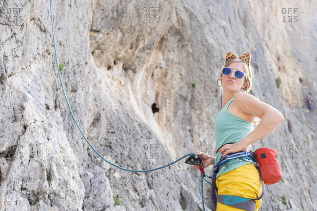 A Woman With Cat Ears Pout At The Camera While Rock Climbing