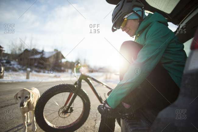 A Woman Sits In Her Car Trunk After A Winter Ride On Fat Bike