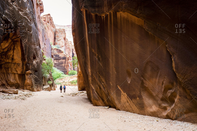 Two Hikers Exploring A Wide Section Of Buckskin Gulch In Southern Utah