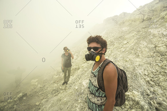 Two Men With Gas Mask Hiking In Volcano Kawah Ijen, Java, Indonesia